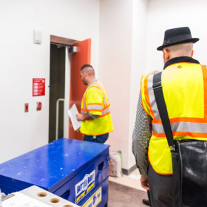 Men wearing safety vests entering door
