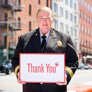 Fire Department Chief holding a sign that says Thank You