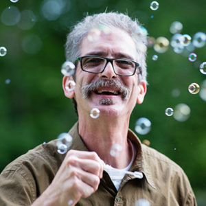 Man with glasses blowing bubbles
