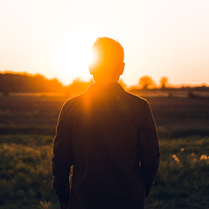 man standing with sun coming over his shoulder